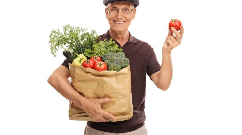 adulto mayor con bolsa de vegetales