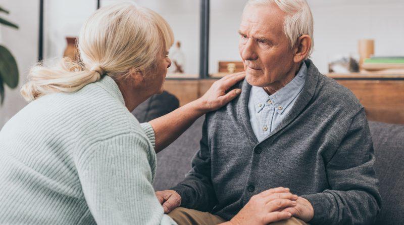 Pareja de jubilados cogidos de la mano y mirando el uno al otro en casa