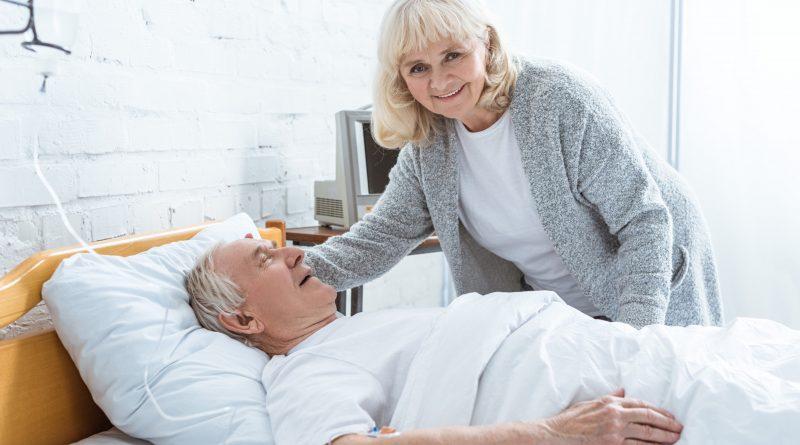 Mujer mayor sonriendo atendiendo a paciente en cama