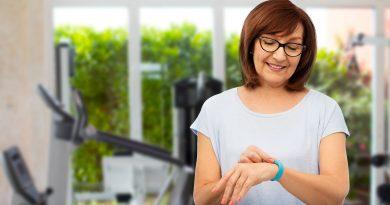 Adulta mayor sonriente con rastreador de fitness en el gimnasio