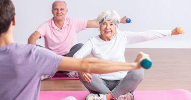 Un par de personas mayores activas durante los ejercicios en el gimnasio con un instructor joven
