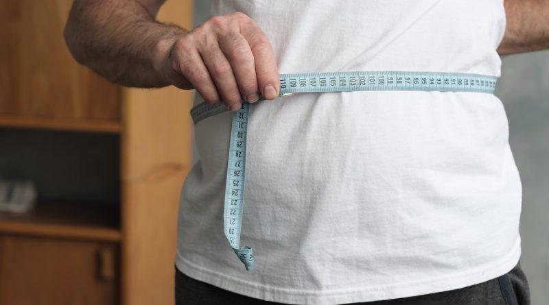 Hombre midiendo su vientre con cinta metrica de pie en la sala de estar