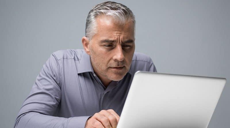 adulto mayor enfrente de una computadora
