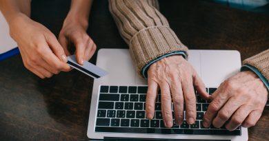 adulto mayor escribiendo en una computadora