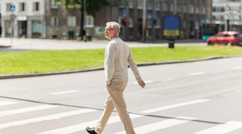 Adulto mayor caminando por el cruce peatonal de la ciudad