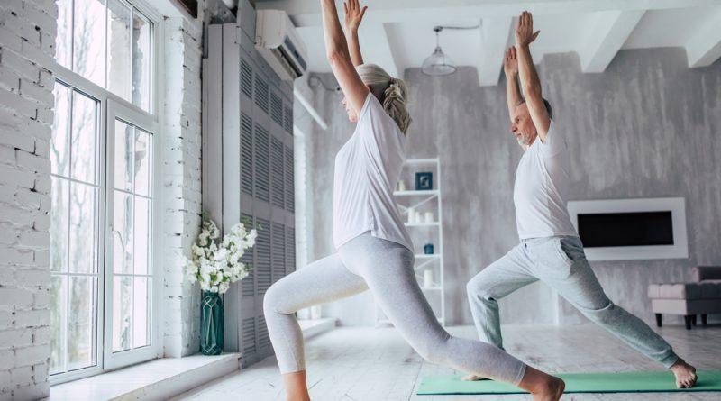 Pareja de adultos mayores realizando posturas de yoga