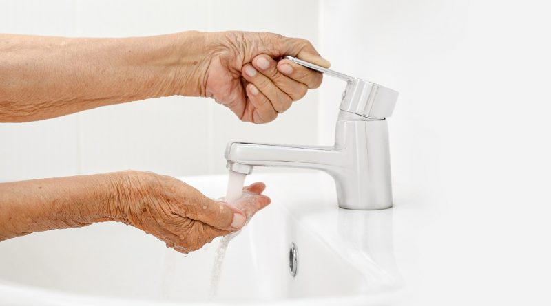 Adulta mayor se lava las mano en cuarto de baño