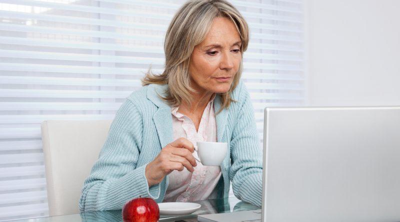 mujer adulta mayor sentada tomando una taza de café frente a un monitor de computadora