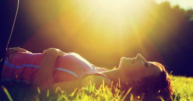 Mujer recostada en el pasto con los ojos cerrados tomando un poco de sol