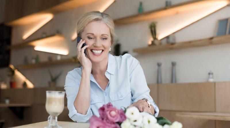 Mujer adulta mayor sonriente y plena con unas flores en la mesa