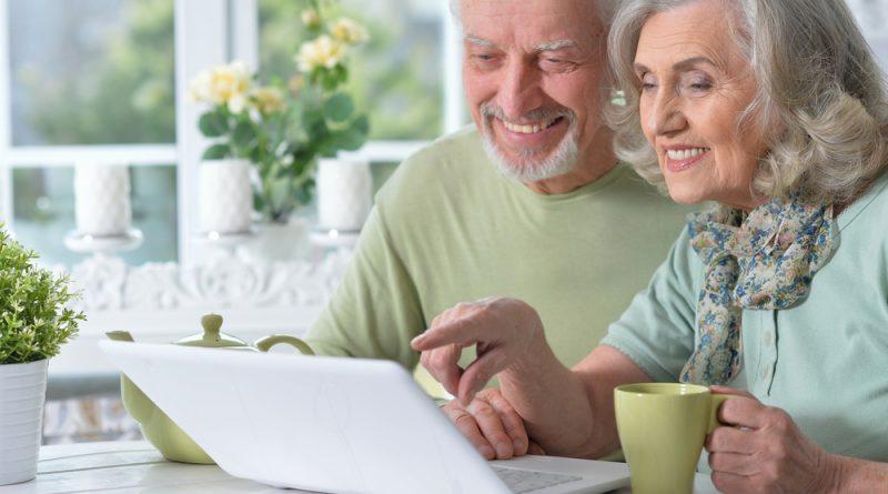 Pareja de adultos mayores sonriendo en la cocina y frente a su computadora