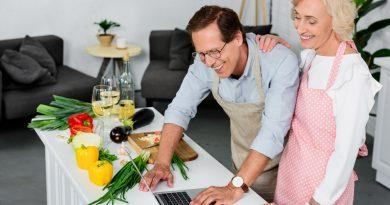 Pareja de adultos mayores en la cocina sonrientes