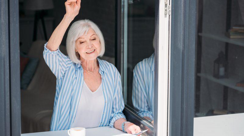 mujer adulta mayor asomada en la ventana con un periódico en la mano y una taza de café