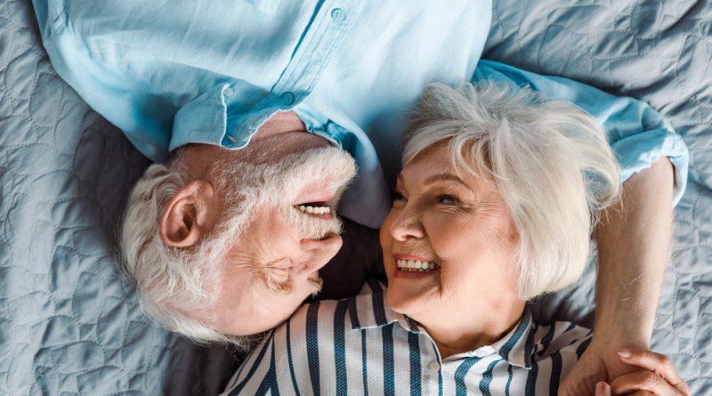 pareja de adultos mayores recostados en la cama felices y sonrientes