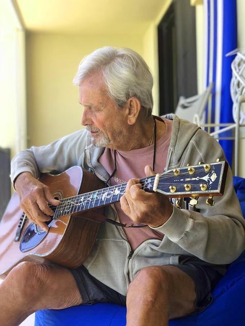 Adulto mayor tocando guitarra.