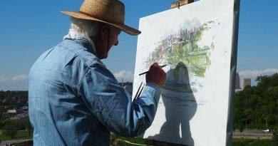 Adulto mayor pintando al aire libre.